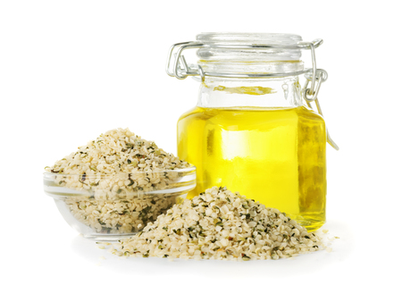 Hemp oil in a bottle and hemp seeds closeup isolated on white background