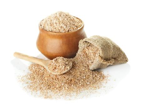 ボウルに、袋、木のスプーンで白い背景のクローズ アップに分離小麦ふすま