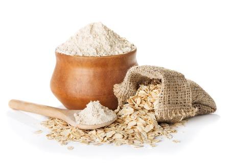 farine d'avoine complet dans un bol et une cuillère, sac avec des flocons d'avoine isolés sur un fond blanc closeup