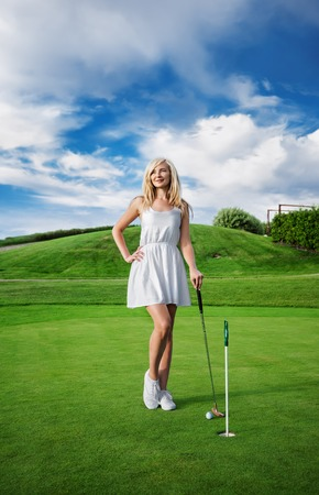 club dress: Young beautiful blond Caucasian woman in white dress playing mini golf in the golf club and looking away on the background of blue sky