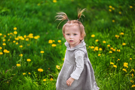 Cute little serious thoughtful girl looking for someone or something on the meadow with dandelions Stock Photo