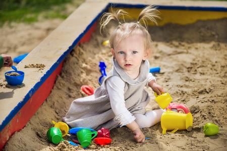 sandbox: Happy little girl playing in a sandbox on the playground