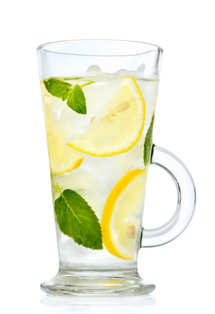 Cold Lemonade, water with lemon, mint and ice in a glass close-up isolated on white background Foto de archivo