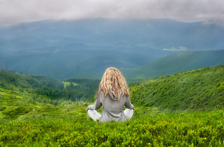 A young blond Caucasian woman meditating in the Carpathian mountains