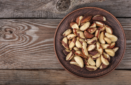 Brazil nuts in a plate on the old wooden background close up top view Stock Photo