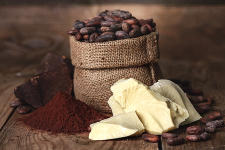 frutas secas: La manteca de cacao e ingredientes para la fabricación de chocolate, el cacao en polvo en el recipiente, los granos de cacao en el fondo de madera vieja