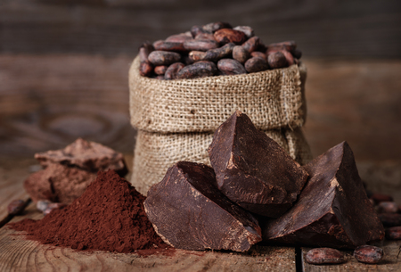 Ongesoete bakblokchocolade, Cacaopoeder en Cacaobonen op oude houten achtergrond