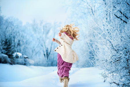 woman with long hair running on winter snowy park