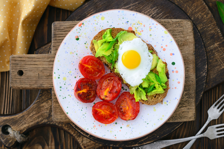 Fried tomatoes and avocado quail egg sandwich in a plate on a wooden background in a rustic style