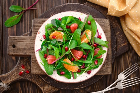 swiss chard, arugula mandarin grapefruit pomegranate spring salad, vegan, vegetarian, raw food and healthy lifestyle concept