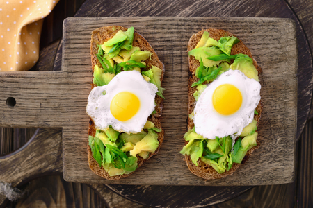 avocado quail egg sandwiches in a plate on a wooden cutting board in a rustic style top view Imagens