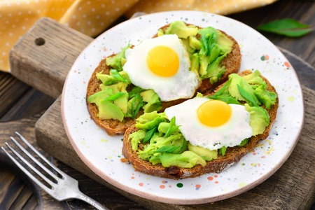 avocado quail egg sandwiches in a plate on a wooden background in a rustic style
