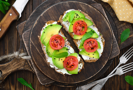 Bright vegan avocado sandwiches on a wooden cutting board close-up, concept of a healthy lifestyle