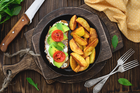 Fried potatoes vegan avocado tomatos sandwiches in a frying panon a wooden cutting boards top view