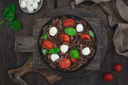 Dark brown buckwheat pasta with mozzarella, cherry tomatoes and basil in a rustic style on an old wooden background Imagens