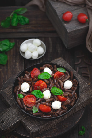 Dark brown buckwheat pasta with mozzarella, cherry tomatoes and basil in a rustic style on an old wooden background Imagens - 75478891