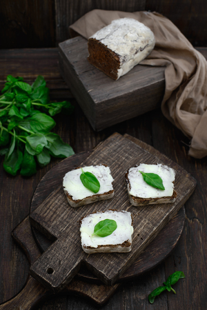 Butter basil Black rye bread Sandwiches on a wooden cutting board close-up, concept of a healthy lifestyle, rustic style Imagens - 75524423