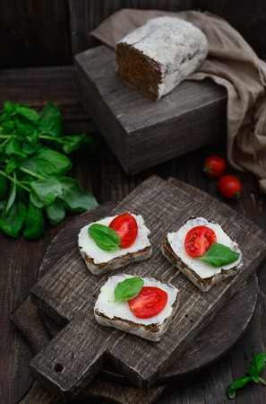 Butter basil Black rye bread tomato Sandwiches on a wooden cutting board close-up, concept of a healthy lifestyle, rustic style