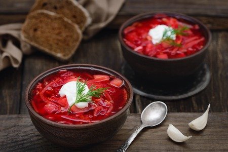 Vegan borscht in bowls on an old wooden background close-up in a rustic style