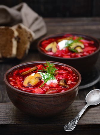 Vegan borscht with mushrooms in bowls on an old wooden background closeup in a rustic style Imagens