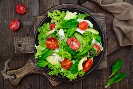 Fresh spring appetizing with Spinach, cress salad, avocado, Peking cabbage, tomatoes and arugula, vegetarian, raw food and healthy lifestyle concept