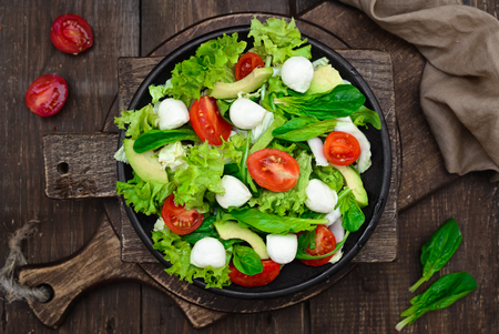 Fresh spring appetizing with Spinach, cress salad, mozzarella, avocado, Peking cabbage, tomatoes and arugula, vegetarian, raw food and healthy lifestyle concept