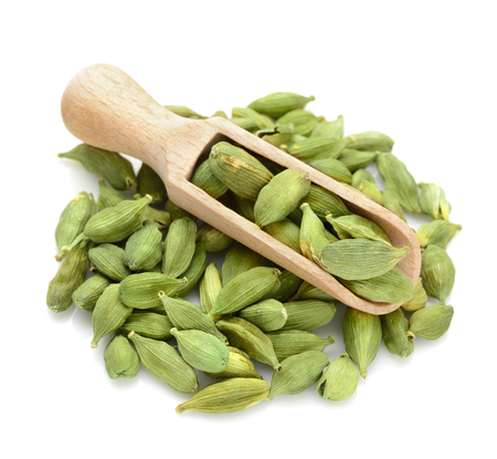 cardamum: green Cardamom, cardamon, cardamum in a scoop for spices close up isolated on a white background