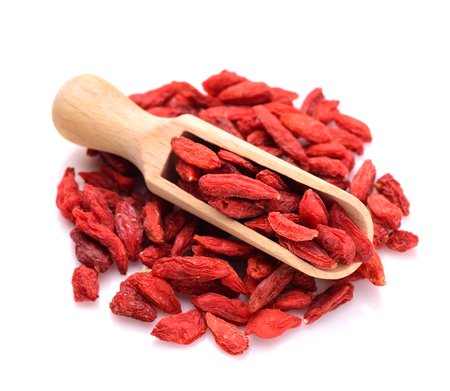 goji berries in a scoop for spices close up isolated on a white background