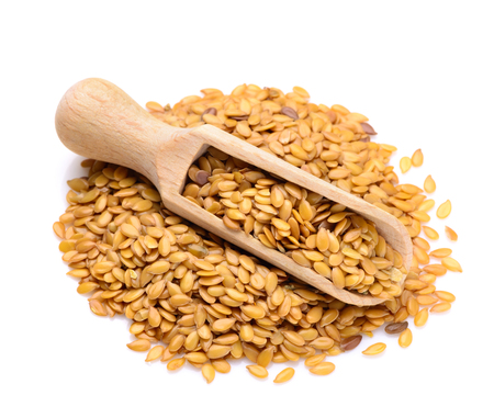 linum: Golden flax seeds in a scoop for spices close up isolated on a white background