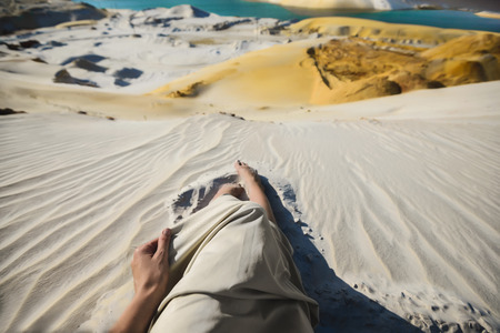 female legs on a sand quarry