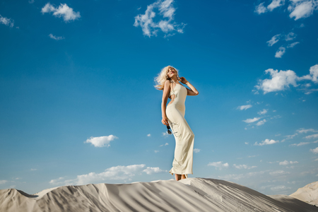 Beautiful caucasian blond woman in the desert in a sexy dress