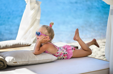 Little Caucasian charming three years old girl lies and tans