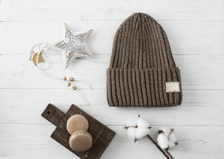 Knitted hats, cotton sprigs, macaroons close-up on a white Imagens - 108721508