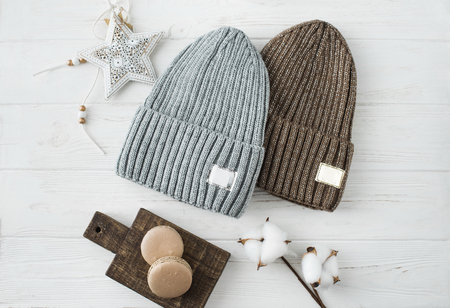 Knitted hats, cotton sprigs, macaroons close-up on a white Imagens