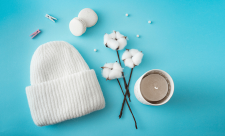 Knitted hat, cotton sprigs, macaroons close-up on a white
