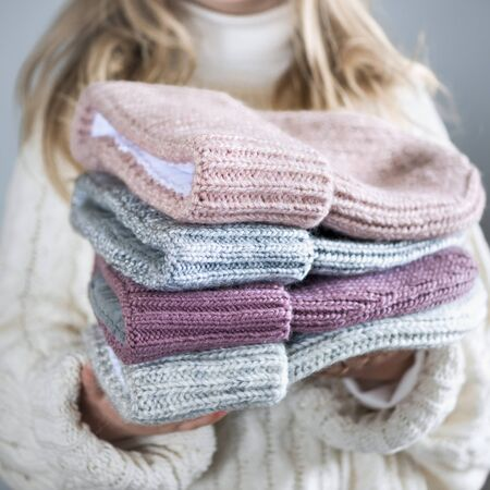 Girl holds winter knitted hats closeup on gray Imagens