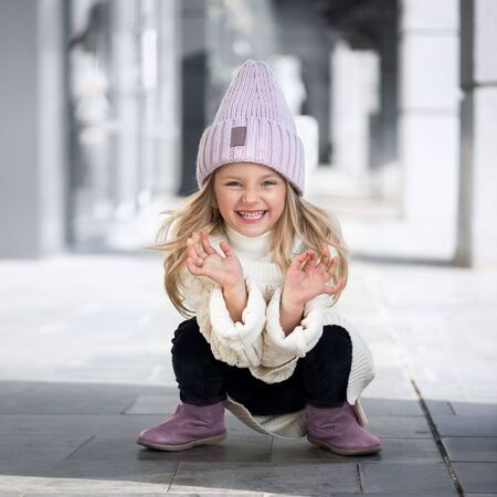 Cute little girl sitting and laughs in knitted hat