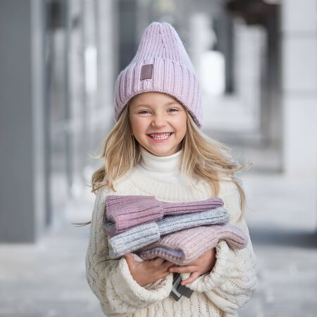 Cute little girl in a knitted lilac hat holding a new knitted hats Imagens
