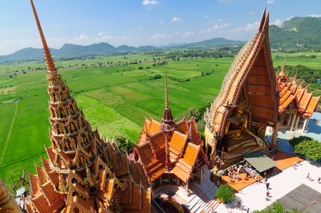 the humanities landscape: The top view of Wat Tham Suea with rice fields and mountain in Kanchanaburi Thailand Stock Photo