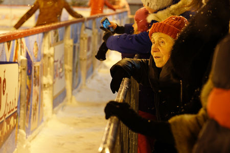 residental care: MOSCOW RUSSIA - 17 January 2016 - The face of an old woman who is watching people skating on the rink on the red Square. A sad sight, and memories of a bygone youth