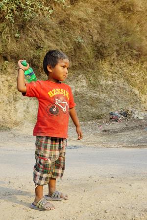 nepali: Pokhara, Nepal - April 24 2016: Serious Nepali boy playing on the road