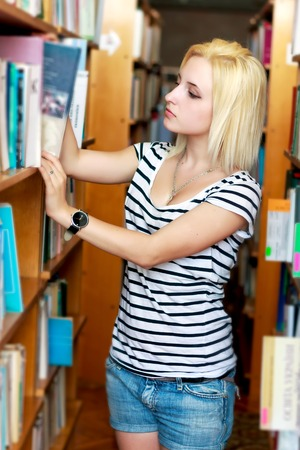 Young cute girl chooses a book from the bookshelf in the library