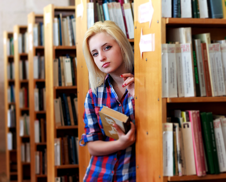 'hide out': Young blonde woman in a shirt with a book in his hand peeking from behind the bookshelves. The interior of the old library.