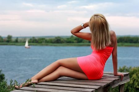 belles jambes: Beauté fille sexy sur la jetée en bois à la recherche du voilier dans la rivière
