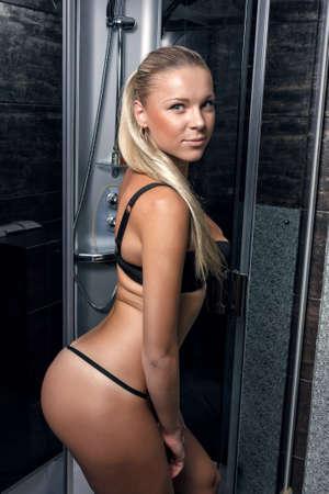 mujer bañandose: Chica en bikini negro es posando con su vista lateral en cabina de ducha
