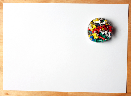 Paper and thumbtacks. A sheet of paper attached to a wooden board office.