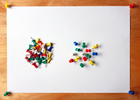 Many colored thumbtacks stuck into a white sheet of paper. A sheet of paper attached to a wooden board office