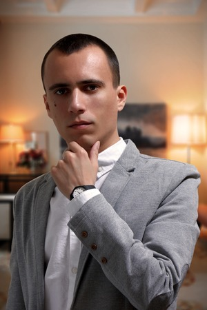 Portrait of goodlooking thoughtful young businessman in gray jacket and white t-shirt, looking at camera. Elegant interior on the background