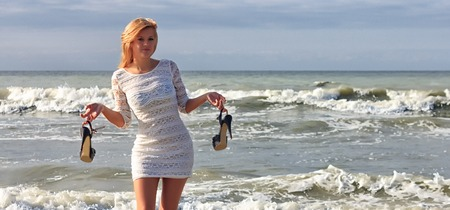Young woman in white dress holding his high heels shoes, standing on beach with sea waves on a background