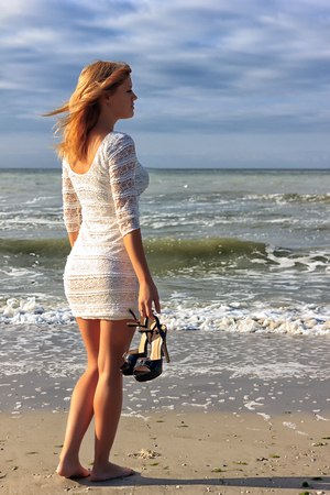 Beautiful young light brown hair woman walking on the beach in white dress at dusk with hugh heel shoes in her hand